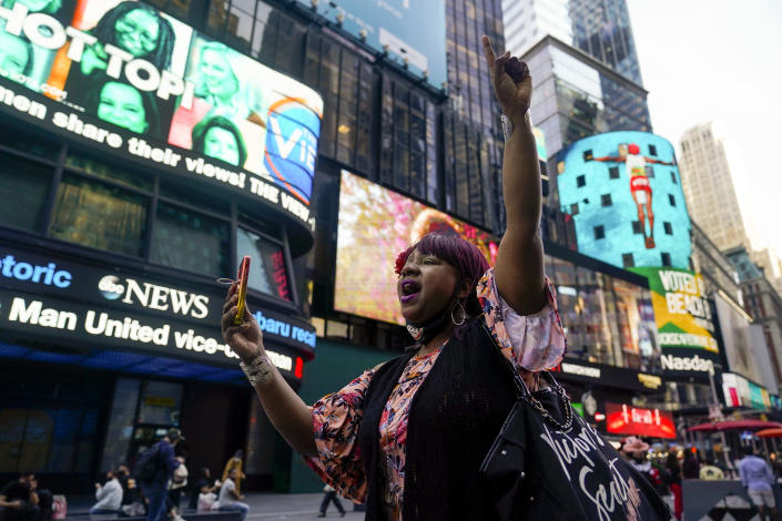 AniYa A motions as she walks through Times Square in New York, while talking on her cell phone after a Minnesota jury found Former Minneapolis police officer Derek Chauvin guilty of murder and manslaughter in the death of George Floyd, Tuesday, April 20, 2021. Floyd died last May after Chauvin, a white officer, pinned his knee on or close to the 46-year-old Black man's neck for about 9 1/2 minutes. (AP Photo/Seth Wenig)