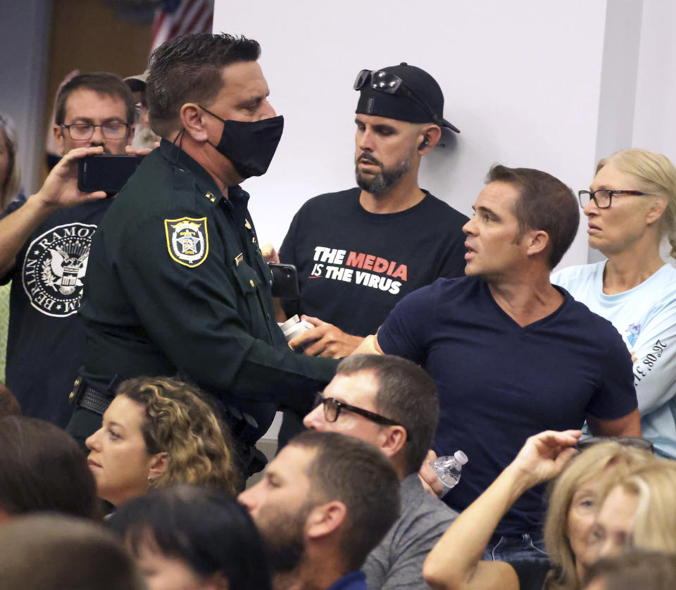 Seminole County, Fla., deputies remove parent Chris Mink of Apopka from an emergency meeting of the Seminole County School Board in Sanford, Fla., Thursday, Sept. 2, 2021. Mink, the parent of a Bear Lake Elementary School student, opposes a call for mask mandates for Seminole schools and was escorted out for shouting during the standing-room only meeting. (Joe Burbank /Orlando Sentinel via AP)