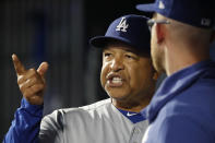 Los Angeles Dodgers manager Dave Roberts, left, talks to a member of his staff between innings of a baseball game against the New York Mets, Sunday, Sept. 15, 2019, in New York. (AP Photo/Kathy Willens)