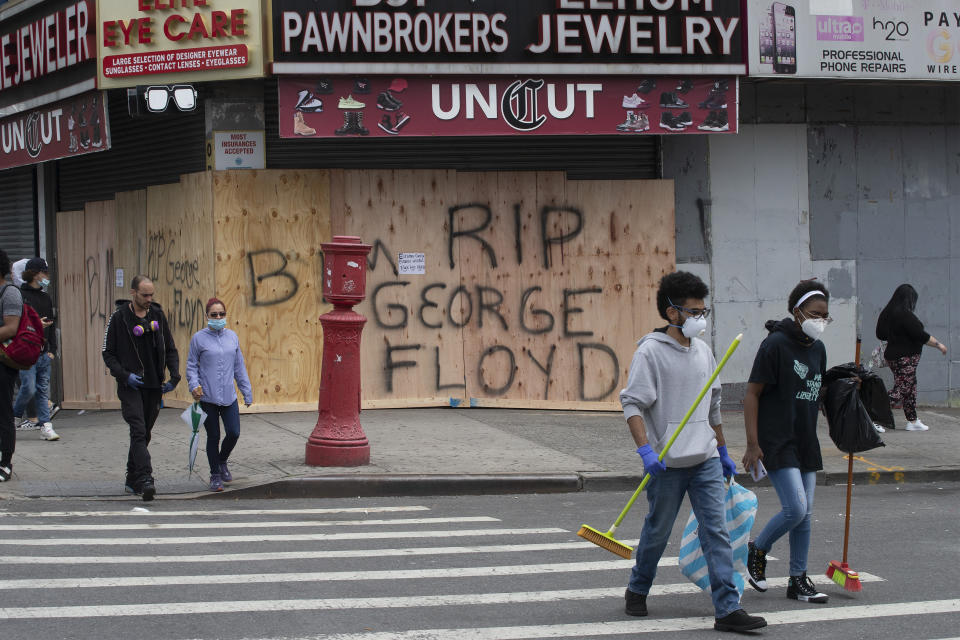 Volunteers Christian Tyler and Ashante West, right, carry brooms after participating in a community cleanup effort as they walk by a boarded up pawnbroker's store, Tuesday, June 2, 2020, in the Fordham Road area of the Bronx borough of New York. Protesters broke into stores Monday night in reaction to George Floyd's death while in police custody on May 25 in Minneapolis. (AP Photo/Mark Lennihan)