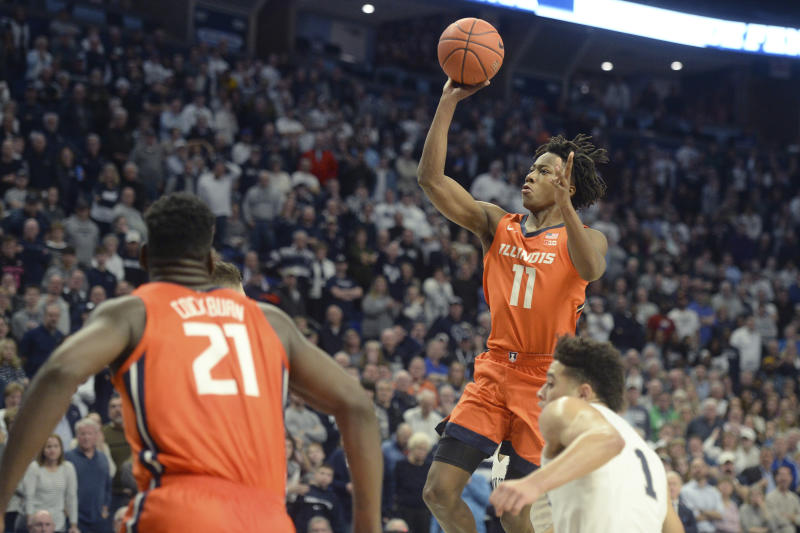 Illinois' Ayo Dosunmu's (11) scored against Penn State in the final minute of an NCAA college basketball game Tuesday, Feb. 18, 2020, in State College, Pa Watching the shot are Illinois' Kofi Cockburn (21) and Penn State's Seth Lundy (1). (AP Photo/Gary M. Baranec)