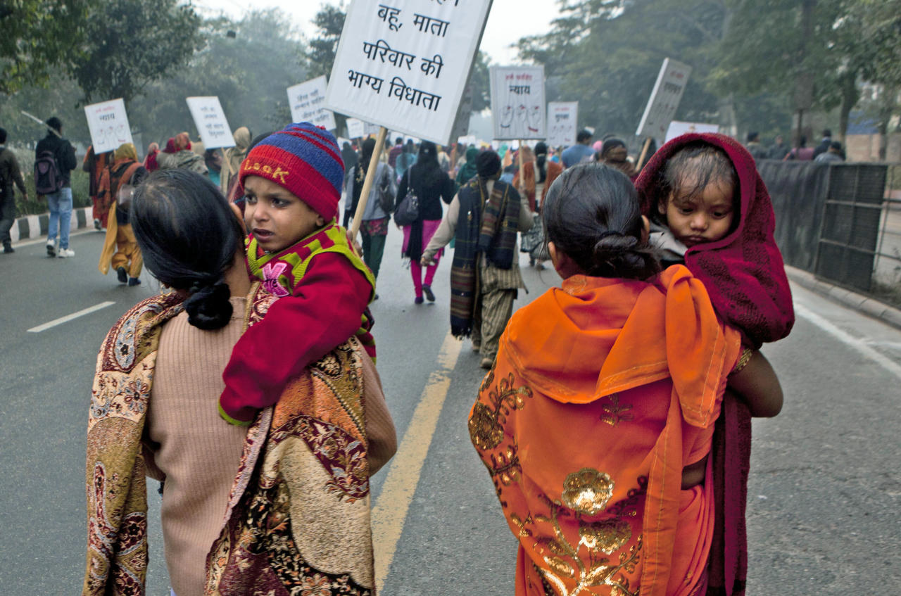 "Indian women carry their children as they march during a protest to mourn the death of a gang rape victim in New Delhi, India, Wednesday, Jan. 2, 2013. India's top court said it will decide whether to suspend lawmakers facing sexual assault charges as thousands of women gathered at the memorial to independence leader Mohandas K. Gandhi to demand stronger protection for their safety. The writing on the sign in foreground reads "" Daughter-in-law, daughter, mother are the ones who decide the fate of the family.""(AP Photo/ Dar Yasin)"
