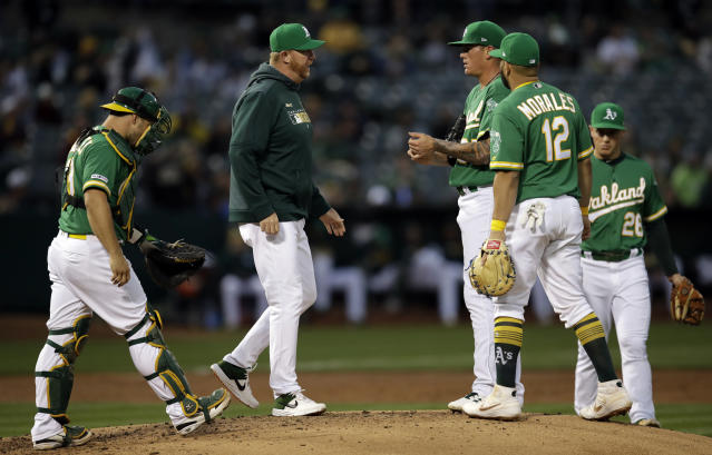 Oakland Athletics pitching coach Scott Emerson, second from left, speaks with pitcher Aaron Brooks in the second inning of a baseball game against the Toronto Blue Jays, Friday, April 19, 2019, in Oakland, Calif. (AP Photo/Ben Margot)