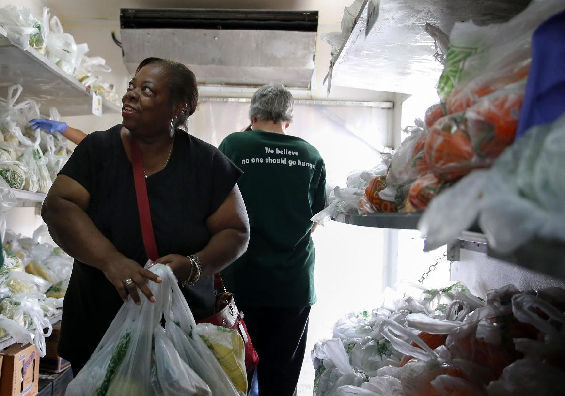 In this Sept. 22, 2016 photo, Carmelita Dorsey looks at fresh fruits and vegetables inside a refrigerator truck at Oak Forest Health Center in Oak Forest, Ill. Six health clinics are working with the Chicago food bank to host a mobile pantry filled with fresh produce. The clinics have hosted 26 'Fresh Truck' visits with the Greater Chicago Food Depository since last year, providing more than 100,000 pounds of fresh fruits and vegetables to more than 3,200 households. (AP Photo/Tae-Gyun Kim)