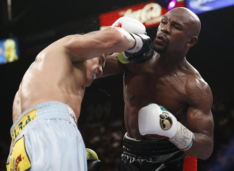 Floyd Mayweather Jr., right, trades punches with Marcos Maidana, from Argentina, in their WBC-WBA welterweight title boxing fight Saturday, May 3, 2014, in Las Vegas. (AP Photo/Eric Jamison)