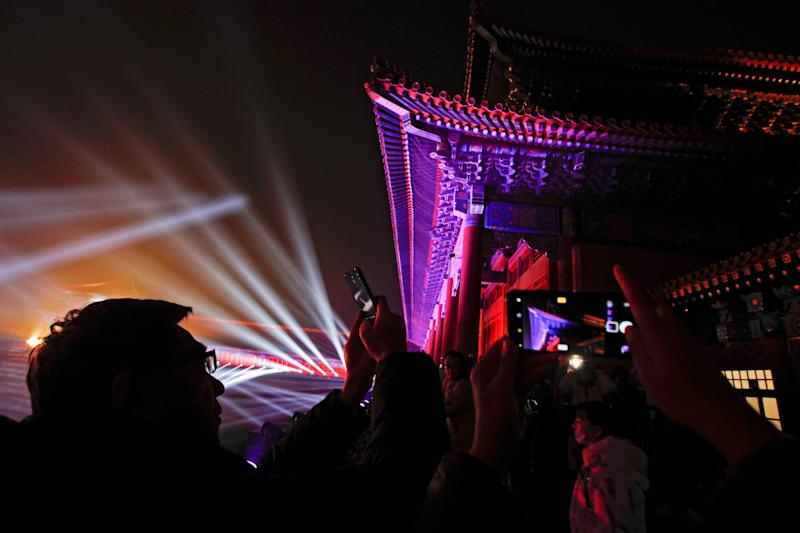 Visitors take souvenir photos of the Forbidden City illuminated with lights during the Lantern Festival in Beijing, Tuesday, Feb. 19, 2019. (Photo: Andy Wong/AP)