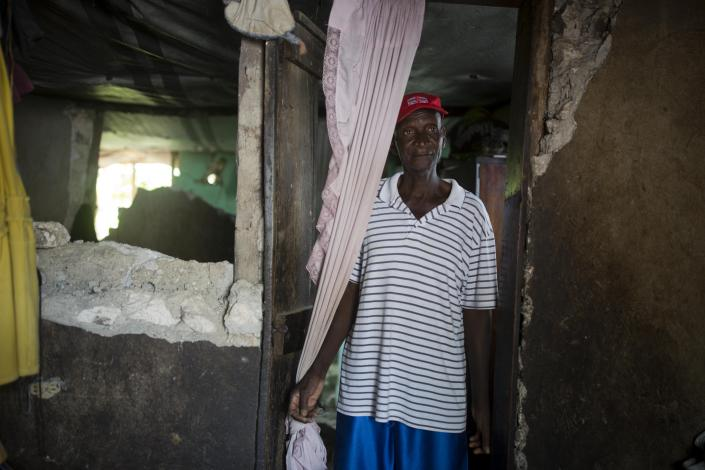 Marcorel Maurice stands inside his home damaged by a magnitude 5.9 earthquake the night before, in Gros Morne, Haiti, Sunday, Oct. 7, 2018. Emergency teams worked to provide relief in Haiti on Sunday after the quake killed at least 11 people and left dozens injured. ( AP Photo/Dieu Nalio Chery)