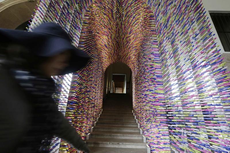 "A woman passes by an installation called ""Transition"", made with lipstick packages, part of the Milan's Furniture Fair, in Milan, Italy, Monday, April 8, 2012. The 52nd International Furniture Fair (Salone del Mobile) opens in Milan on Tuesday, April 9, 2013 until April 14. (AP Photo/Luca Bruno)"