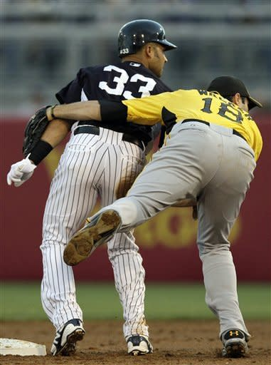 Pittsburgh Pirates second baseman Neil Walker holds onto New York Yankees Nick Swisher (33) as they look toward first after Robinson Cano grounded into a double play during the first inning of their spring training baseball game at Steinbrenner Field in Tampa, Fla., Tuesday, March 20, 2012. (AP Photo/Kathy Willens)