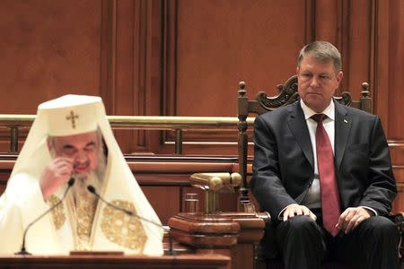 Romania's new President Iohannis listens to a blessing of Romanian Orthodox Patriarch Daniel after his swearing-in ceremony in front of the Parliament in Bucharest