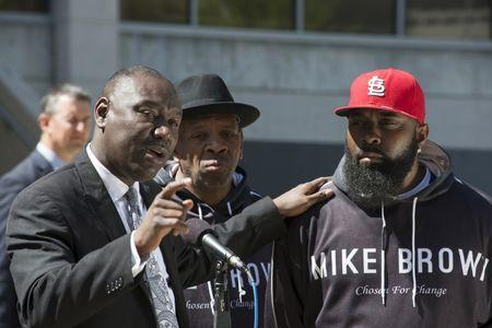 Michael Brown's family attorney Benjamin Crump puts his hand on the shoulder of Michael Brown Sr. during the announcement the Brown family has filed a wrongful death lawsuit against the city of Ferguson in front of the St. Louis County Circuit Court in Clayton, Missouri, April 23, 2015. REUTERS/Kate Munsch