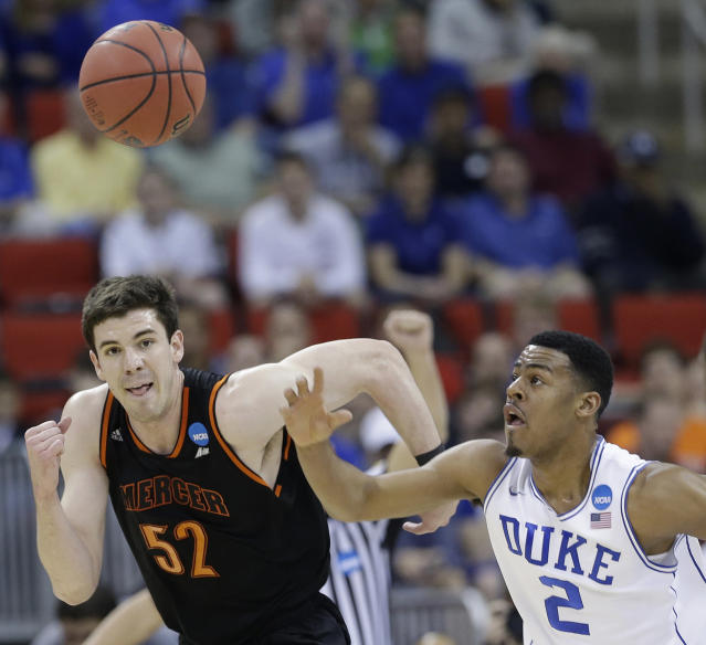 Duke guard Quinn Cook (2) and Mercer forward Daniel Coursey (52) vie for a loose ball during the first half of an NCAA college basketball second-round game, Friday, March 21, 2014, in Raleigh, N.C. (AP Photo/Gerry Broome)