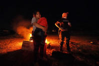 Katelyn Smith holds her one-year-old son son Ricky Trahan III, while talking with Tiffany Theriot, founder of the charity Cajun Commissary, as they stand next to a fire amidst the rubble of the family's destroyed home in Lake Charles, La., Friday, Dec. 4, 2020. They were hit by Hurricanes Laura and Delta. Her future in-laws are living in a tent on the property, while she, her child and her fiancé Ricky Trahan, Jr., are living in a camper loaned by Tiffany. A relatives home on the same property is now gutted and they are living in a camper as well. (AP Photo/Gerald Herbert)
