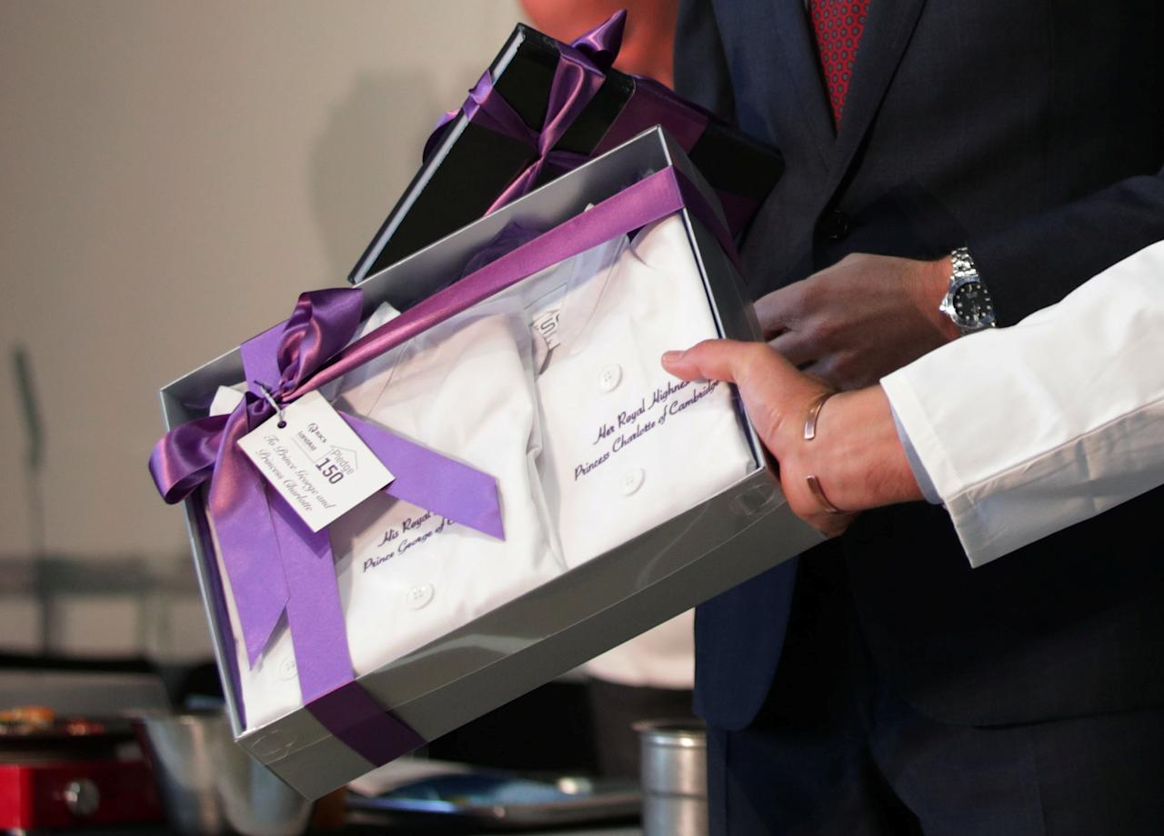 Britain's Prince William is presented with a gift of little chef outfits for Prince George and Princess Charlotte by Sean Tompkins, CEO of the Royal Institution of Chartered Surveyors, at the launch of LandAid's Pledge150 campaign, in London, Britain, November 17, 2017. REUTERS/Yui Mok/Pool