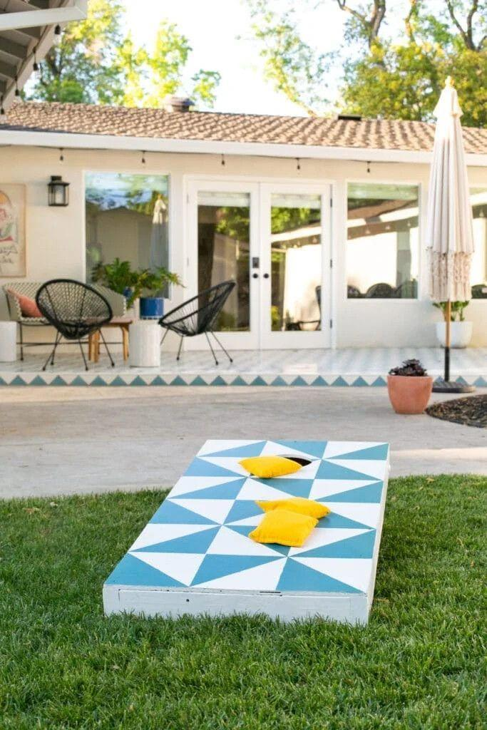 """<p>Cornhole boards are so easy to personalize. Check out this tutorial for a few DIY tips to try. Consider decorating your boards with a token that symbolizes a favorite family memory, vacation spot, or sports team. </p><p><strong>Get the tutorial at <a href=""""https://lovelyindeed.com/diy-cornhole-game-paint-giveaway/"""" rel=""""nofollow noopener"""" target=""""_blank"""" data-ylk=""""slk:Lovely Indeed"""" class=""""link rapid-noclick-resp"""">Lovely Indeed</a>. </strong></p><p><a class=""""link rapid-noclick-resp"""" href=""""https://www.amazon.com/LICHAMP-10-Piece-Painters-Multi-Yards/dp/B07THL91MS/?tag=syn-yahoo-20&ascsubtag=%5Bartid%7C2164.g.36687460%5Bsrc%7Cyahoo-us"""" rel=""""nofollow noopener"""" target=""""_blank"""" data-ylk=""""slk:SHOP PAINTER'S TAPE"""">SHOP PAINTER'S TAPE</a></p>"""