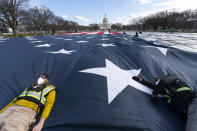 Workers use their body weight to hold down a large American flag placed on the National Mall, with the U.S. Capitol behind them, ahead of the inauguration of President-elect Joe Biden and Vice President-elect Kamala Harris, Monday, Jan. 18, 2021, in Washington. (AP Photo/Alex Brandon)