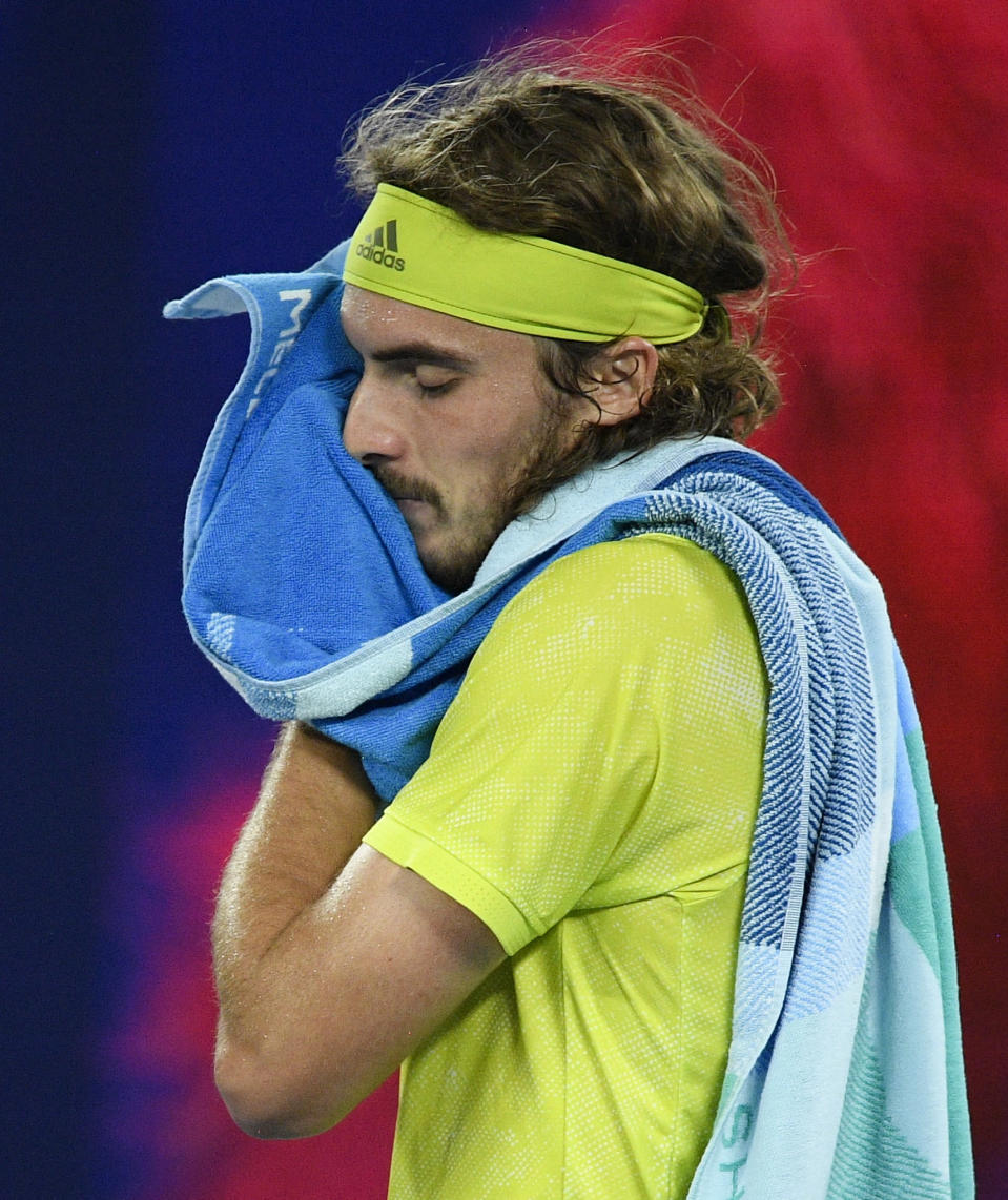 Greece's Stefanos Tsitsipas wipes the sweat from his face during his semifinal against Russia's Daniil Medvedev at the Australian Open tennis championship in Melbourne, Australia, Friday, Feb. 19, 2021.(AP Photo/Andy Brownbill)