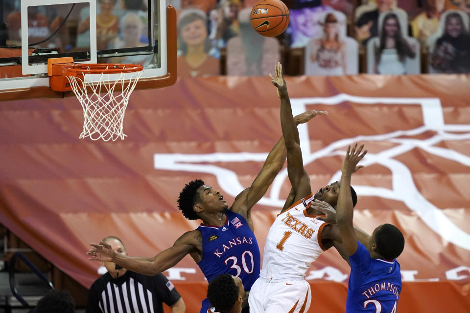 Texas guard Andrew Jones (1) drives to the basket between Kansas guard Ochai Agbaji (30) and guard Bryce Thompson, right, during the second half of an NCAA college basketball game, Tuesday, Feb. 23, 2021, in Austin, Texas. (AP Photo/Eric Gay)