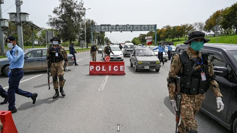 Security personnel wearing facemasks check commuters at a checkpoint of the city's entrance during a government-imposed nationwide lockdown as a preventive measure against the COVID-19 coronavirus in Islamabad
