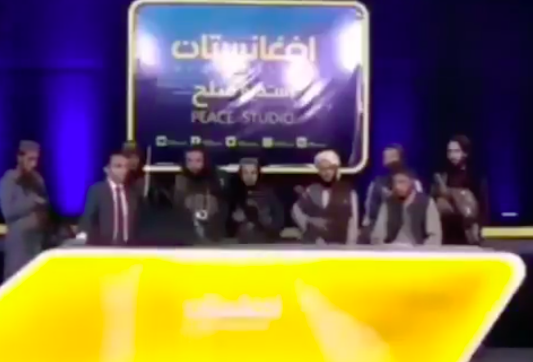 A number of armed Taliban fighters flank the news anchor. (Peace Studio/Twitter)