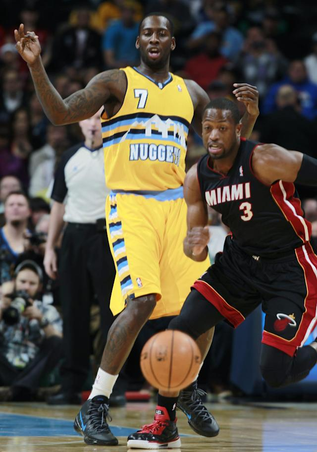 Miami Heat guard Dwyane Wade, front, steals ball from Denver Nuggets forward J.J. Hickson in the first quarter of an NBA basketball game in Denver on Monday, Dec. 30, 2013. (AP Photo/David Zalubowski)