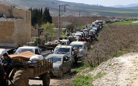 Syrian civilians ride their cars through Ain Dara in Syria's northern Afrin region as they flee Afrin city on March 12 - Credit: AFP