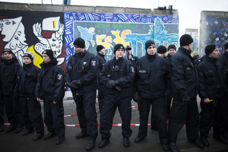 German police officers protect a part of the former Berlin Wall in Berlin, Germany, Friday, March 1, 2013. Berliners are protesting as a construction company removes a section of a historic stretch of the Berlin Wall known as the East Side Gallery to provide access to a riverside plot where luxury condominiums are being built. Since German reunification, the stretch of the wall has been preserved as a historical monument and transformed into an open air gallery painted with colorful murals, and has become a popular tourist attraction. (AP Photo/Markus Schreiber)