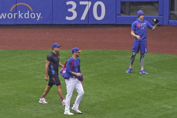 From left, New York Mets relief pitcher Edwin Diaz, pitcher Joey Lucchesi and starting pitcher Jacob deGrom stand on the field after a baseball game against the Atlanta Braves was postponed due to rain, Sunday, May 30, 2021, in New York. Sunday's game was rescheduled as part of a single-admission doubleheader on July 26. (AP Photo/Kathy Willens)