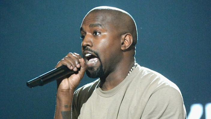 """Kanye West accepts the Video Vanguard Award onstage during the 2015 MTV Video Music Awards. His apparel firm, Yeezy, was among the companies approved for a government loan program aimed at reducing layoffs during the pandemic. <span class=""""copyright"""">(Jeff Kravitz / MTV1415/FilmMagic)</span>"""