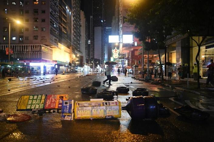 A pedestrian (C) walks past debris littering the street after protesters clashed with police in the Wanchai district in Hong Kong (AFP Photo/Mohd RASFAN)