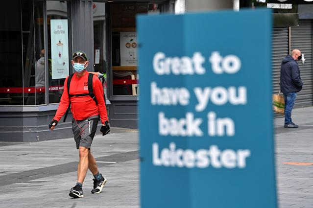 Shoppers wearing PPE walk in the centre of Leicester as the city goes into lockdown. (Getty)