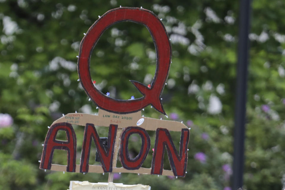 "FILE - In this May 14, 2020, file photo, a person carries a sign supporting QAnon at a protest rally in Olympia, Wash. Facebook said Tuesday, Oct. 6, 2020, that it will remove Facebook pages, groups and Instagram accounts for ""representing QAnon."" (AP Photo/Ted S. Warren, File)"