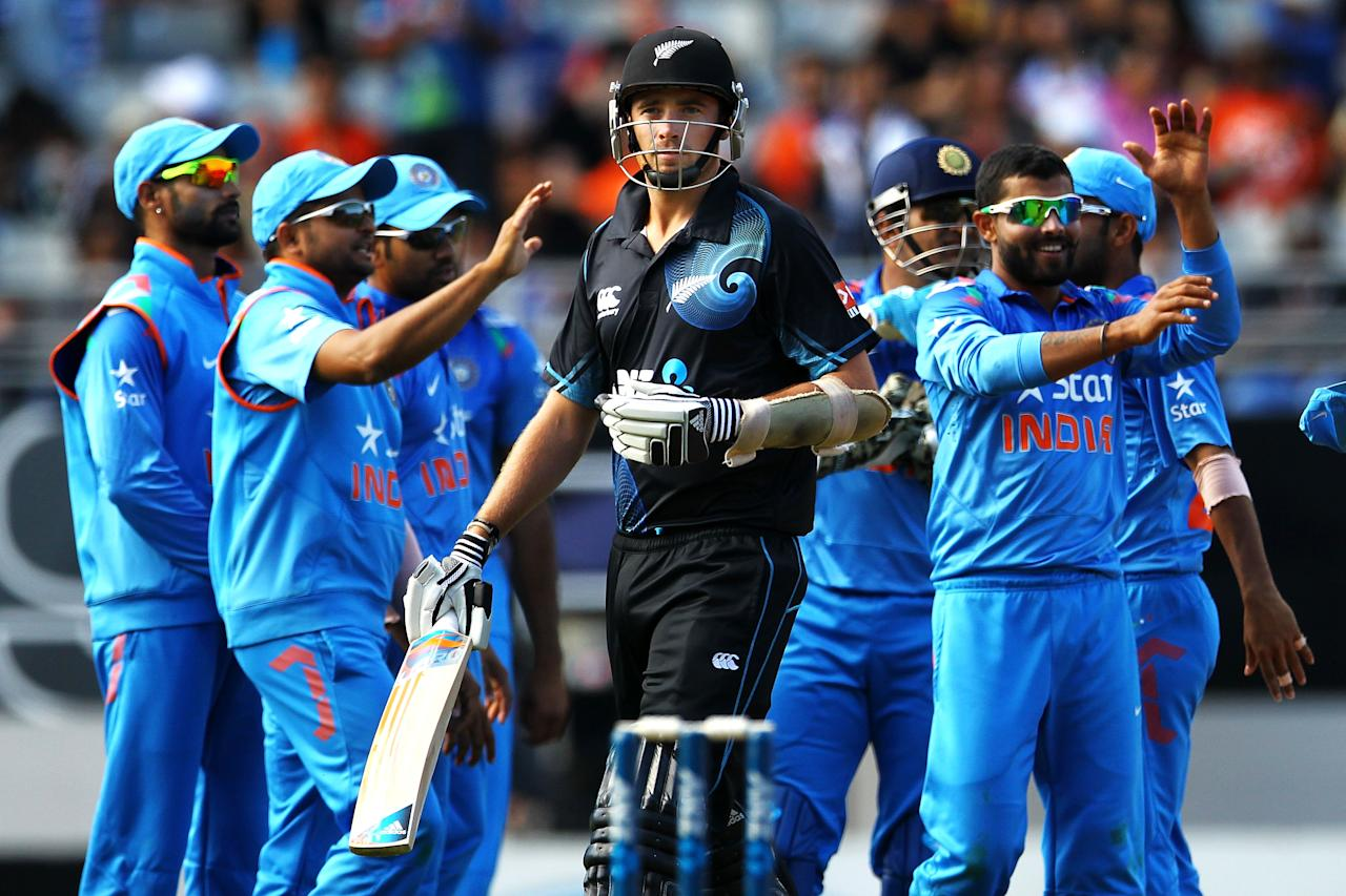 AUCKLAND, NEW ZEALAND - JANUARY 25: Tim Southee of New Zealand looks on as Indian players celebrate the wicket of Luke Ronchi of New Zealand during the One Day International match between New Zealand and India at Eden Park on January 25, 2014 in Auckland, New Zealand.  (Photo by Anthony Au-Yeung/Getty Images)