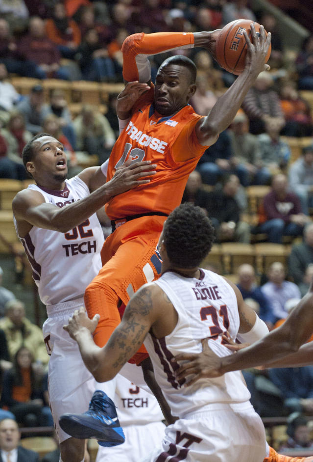 Syracuse's Baye Moussa Keita grabs a rebound against Virginia Tech's Trevor Thompson, left, during the first half of an NCAA college basketball game Tuesday, Jan. 7, 2014, in Blacksburg, Va. (AP Photo/Don Petersen)
