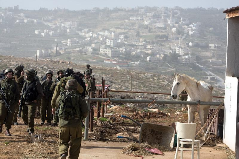 Israeli solders gather at the site of a stabbing attack on January 18, 2016 in the Tekoa settlement, south of Jerusalem (AFP Photo/Menahem Kahana)