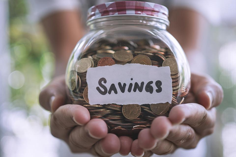 Person holding a jar of change labeled savings