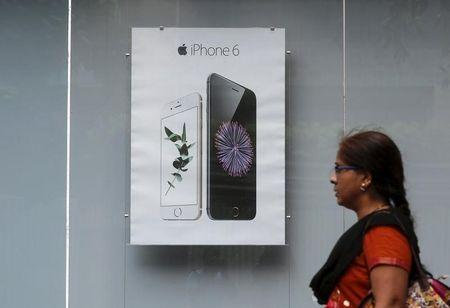 A pedestrian walks past an Apple iPhone 6 advertisement at an electronics store in Mumbai, India