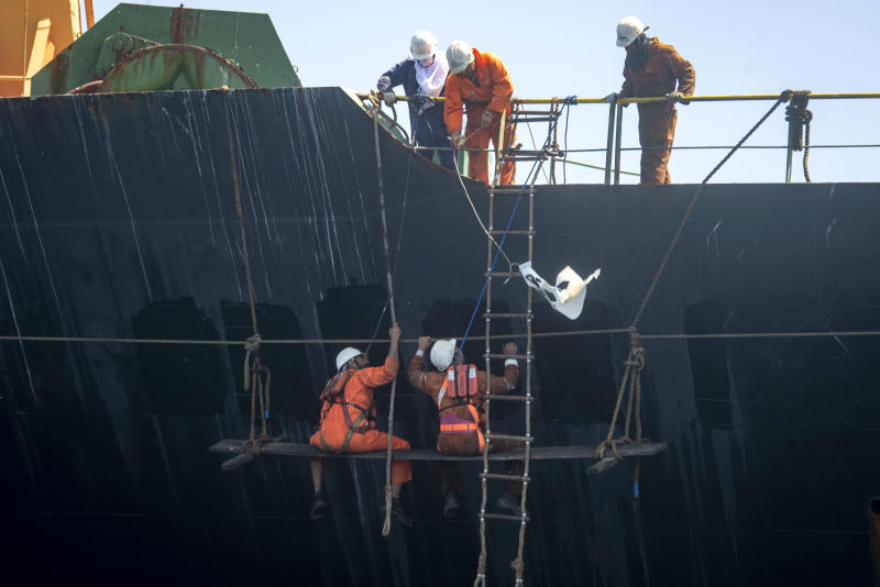 """Crew members of the Grace 1 super tanker remove the name of ship in the British territory of Gibraltar, Saturday, Aug. 17, 2019. The shipping agent for an Iranian supertanker caught in a diplomatic standoff says the vessel is ready to depart Gibraltar in """"24 to 48 hours,"""" despite a last-minute effort by the United States to seize it again. (AP Photo/Marcos Moreno)"""