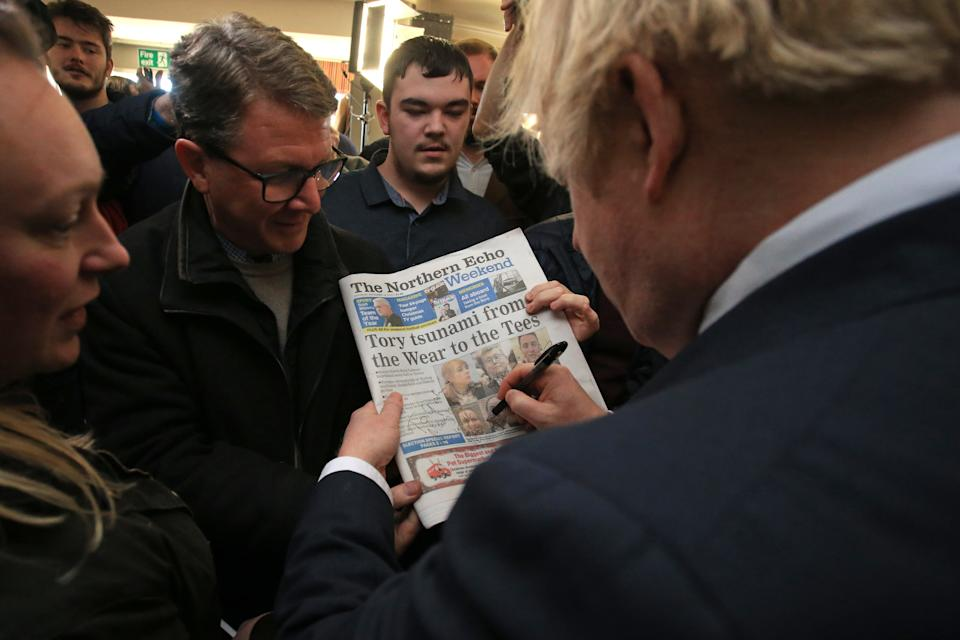 Prime Minister Boris Johnson signs a copy of The Northern Echo for a supporter during a visit to see newly elected Conservative party MP for Sedgefield, Paul Howell during a visit to Sedgefield Cricket Club in County Durham.