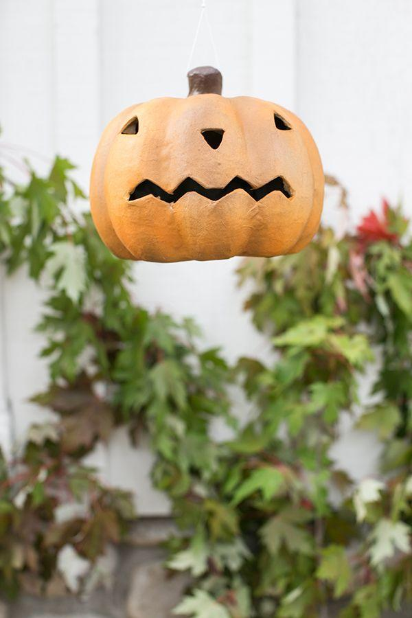 "<p>Make pumpkin lanterns out of paper maché and hang them on white string so it looks like they're floating. Light them up with battery-operated tea lights.</p><p>See more at <a href=""https://sugarandcharm.com/2017/10/a-charming-and-traditional-halloween-party.html?section-36"" rel=""nofollow noopener"" target=""_blank"" data-ylk=""slk:Sugar and Charm"" class=""link rapid-noclick-resp"">Sugar and Charm</a>.</p>"