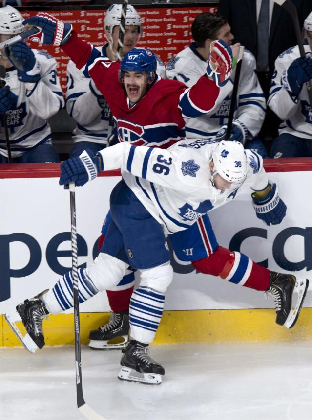 Montreal Canadiens' Max Pacioretty reacts as he is hip checked into the boards by Toronto Maple Leafs' Carl Gunnarsson (36) during the first period of an NHL hockey game Saturday, Nov. 30, 2013 in Montreal. (AP Photo/The Canadian Press, Paul Chiasson)