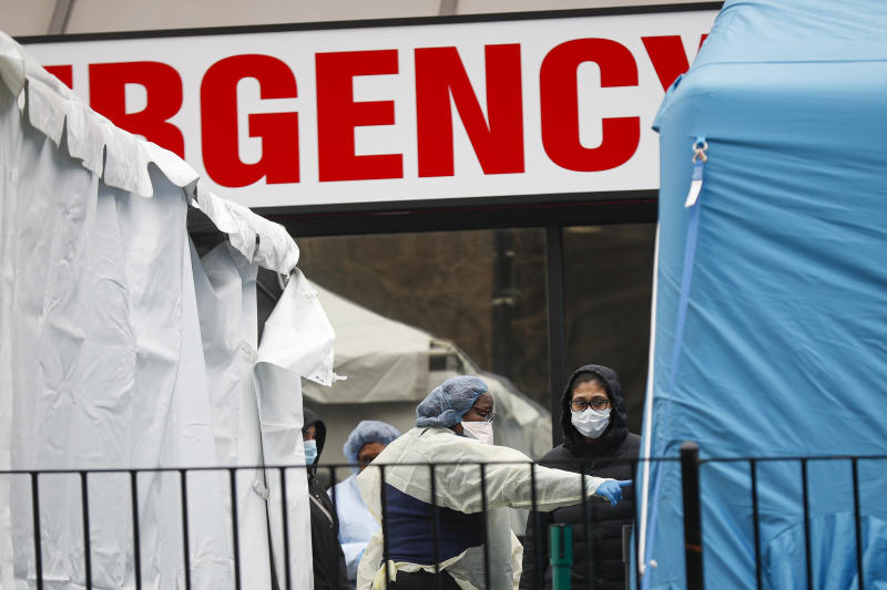 A medical worker directs a patient to enter a COVID-19 testing site at Elmhurst Hospital Center, Wednesday, March 25, 2020, in New York. Gov. Andrew Cuomo sounded his most dire warning yet about the coronavirus pandemic Tuesday, saying the infection rate in New York is accelerating and the state could be as close as two weeks away from a crisis that sees 40,000 people in intensive care. Such a surge would overwhelm hospitals, which now have just 3,000 intensive care unit beds statewide. (AP Photo/John Minchillo)