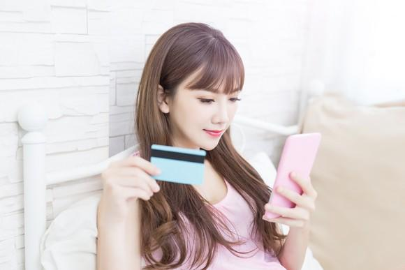 A young woman shops on her smartphone.