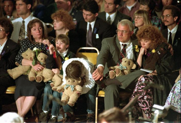FILE - In this Sunday, April 23, 1995 file photo, an unidentified boy leans over during the prayer service where some 20,000 people overflowed the State Fairgrounds. President Clinton and the Rev. Billy Graham addressed the memorial service on what the president declared a national day of mourning. (AP Photo/Beth A Keiser)
