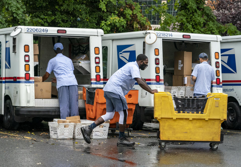 Letter carriers load mail trucks for deliveries at a U.S. Postal Service facility in McLean, Va., Friday, July 31, 2020. (AP Photo/J. Scott Applewhite)