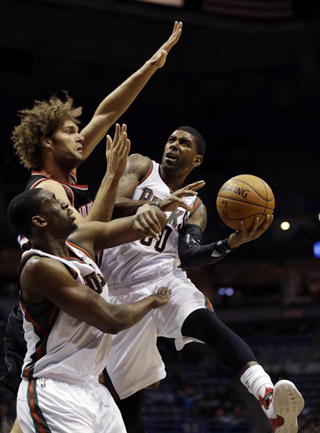 Milwaukee Bucks' O.J. Mayo (00) drives against Portland Trail Blazers' Robin Lopez during the second half of an NBA basketball game Wednesday, Nov. 20, 2013, in Milwaukee. (AP Photo/Jeffrey Phelps)