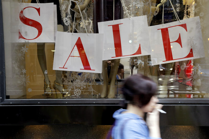 "In this Tuesday, Dec. 18, 2012, photo, a person passes a retail store with sale sign displayed in the window in Philadelphia. When it comes to big discounts, better late than never. This holiday shopping season, stores haven't been offering the same big discounts as they did in previous years as they tried to lure shoppers in with other incentives,but during the final days leading up to Christmas, shoppers will see more of those jaw-dropping ""70 percent off"" sale signs as stores try to salvage a season that so far has been disappointing.  (AP Photo/Matt Rourke)"