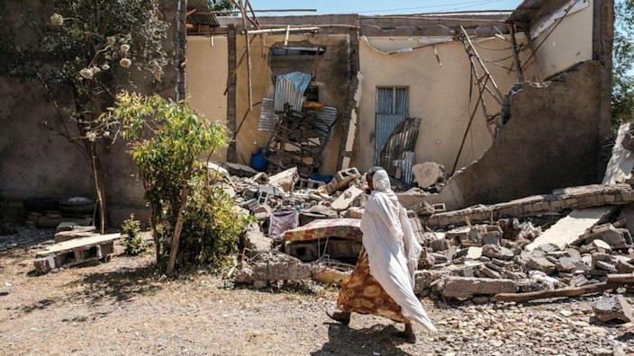 A woman walks in front of a damaged house which was shelled as federal-aligned forces entered the city, in Wukro, north of Mekele, on March 1, 2021