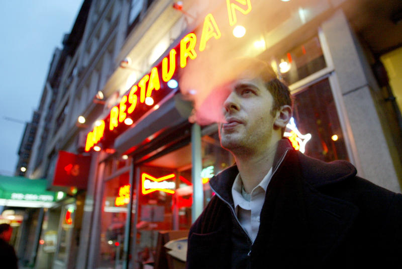 FILE - In this April 8, 2003 file photo, David Ozanich of Brooklyn smokes outside the Live Bait bar in New York after a city-wide ban on smoking in bars and restaurants went into effect. Laws banning smoking in restaurants, bars and workplaces have been implemented in places across the country. (AP Photo/Diane Bondareff, File)