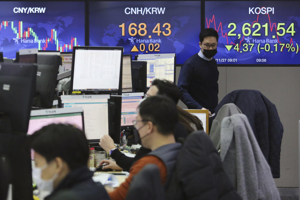 A currency trader passes by screens showing the Korea Composite Stock Price Index, right, and the foreign exchange rate at the foreign exchange dealing room of the KEB Hana Bank headquarters in Seoul, South Korea, Friday, Nov. 27, 2020. Asian stock markets declined Friday as questions about the effectiveness of one possible coronavirus vaccine weighed on investor optimism. (AP Photo/Ahn Young-joon)